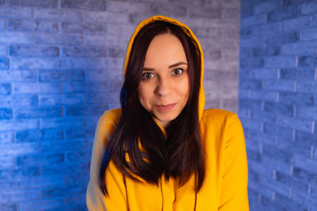 A young woman in a fashionable yellow hoodie. Portrait of a beautiful woman in a yellow hoodie against background of brick wall.