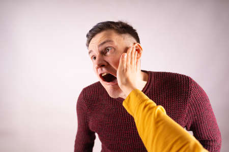 Crop person slapping scared man in face. Emotional male getting slapped in face while shouting with closed eyes in fear on white background.