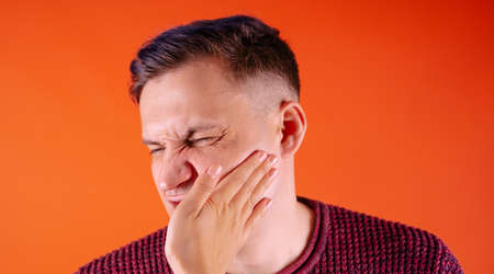 Crop person slapping scared man in face. Emotional male getting slapped in face while shouting with closed eyes in fear on orange background.
