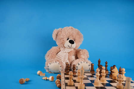 Close up of teddy bear with chess pieces on chessboard. Soft plush toy playing chess on blue background Stockfoto