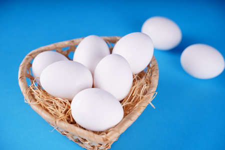 Farm raw, fresh white chicken egg in a basket on a blue background. Concept: a fresh egg for the morning breakfast