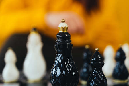 Selective focus of beautiful chess on chessboard in room. Close up of body part of unrecognizable woman playing in board game
