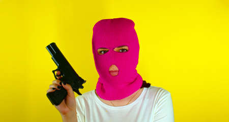 Unrecognizable woman in pink balaclava with gun on yellow background. Dangerous criminal in mask with pistol looking at camera