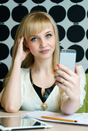 Blonde girl sitting in cafe holds a smartphone Stock Photo