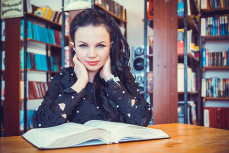 Cute young model girl sitting at table holding book posing for camera at library