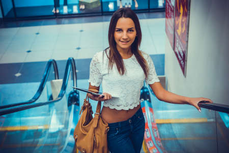 Attractive girl holding silver computer tablet goes up on escalator at boutique Stock fotó
