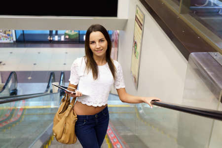 Positive young european model holding silver computer tablet goes up on escalator at boutique Stock fotó
