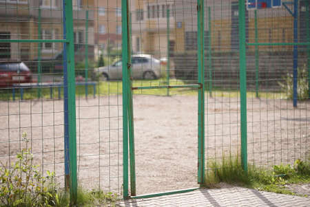 Broken steel mesh of metal fence of a basketball court in residential neighborhood in summer