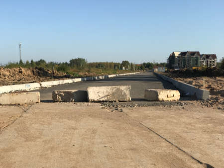 Road blocked with concrete blocks across the road to the construction site Stock fotó