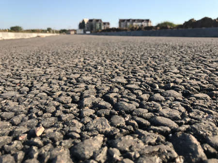 Rough asphalt pavement in the summer season. Close-up Stock fotó