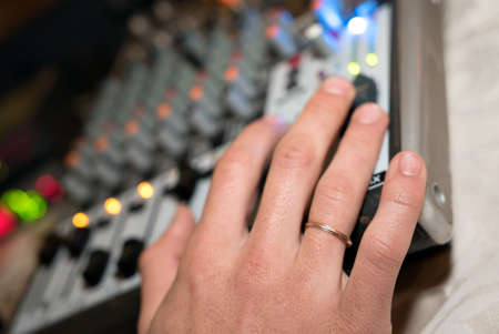 DJ working on a audiomixer at a nightclub. Close-up of hands adjusting quality of music using a knobs of the audio mixer Stock fotó