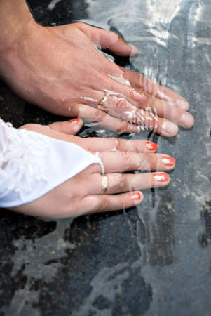 Close-up of hands of bride and groom with wedding rings on marble stone of fountain in water in summer