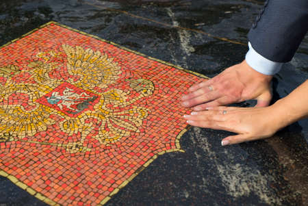 Close-up of hands of bride and groom with wedding rings on marble stone of fountain in water with image of Russia coat of arms in summer.