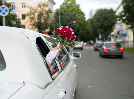 Unidentified bride stuck out her hand with the red bouquet from the window of the decorated white car and lightly waving it on warm summer day. Stock fotó
