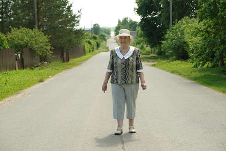 Old mature woman walking on the road at the sunny day. Positive emotions in lifestyle Stock fotó