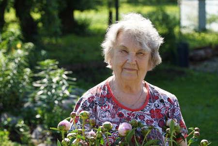 昔の笑顔と呼ばれる牡丹のような花を成長の背景の公園で女性の肖像画。女性が自然のエネルギーを充電します。