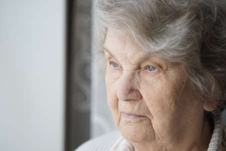 Portrait of serious old elderly woman aged 80s indoors. Close-up