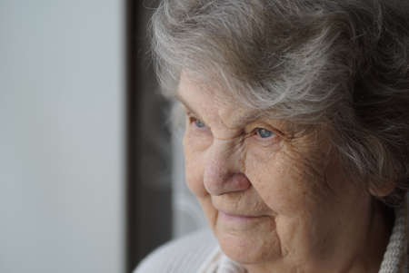 Portrait of smiling mature elderly woman aged 80s indoors. Close-up