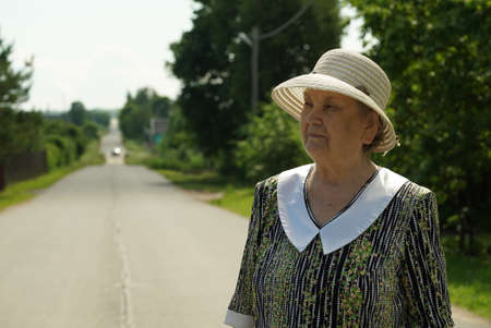 Portrait of serious old elderly woman aged 80s dressed in hat outdoors in the background of road. Slow Motion