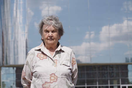 Portrait of serious mature old woman aged 80s outdoors in the background skyscraper with reflective mirror surface in summer