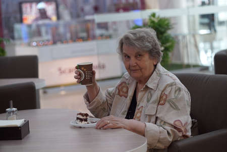Portrait of old elderly smiling woman dressed in grey cotton shirt sitting in cafe holding cup of coffee. Wonderful mood