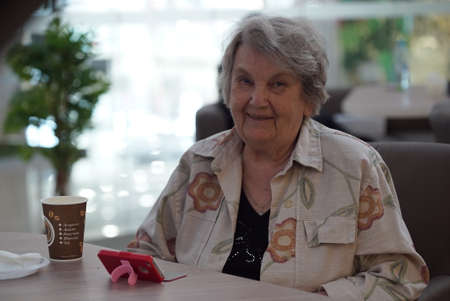 Portrait of old elderly smiling woman dressed in grey cotton shirt sitting in cafe. Communication over smart phone with relatives. Wonderful mood