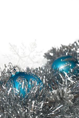 a pair of blue christmas balls and a pair of snowflakes on silver tinsel photo