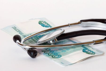 paid medicine: Stethoscope and banknotes on a white background close-up