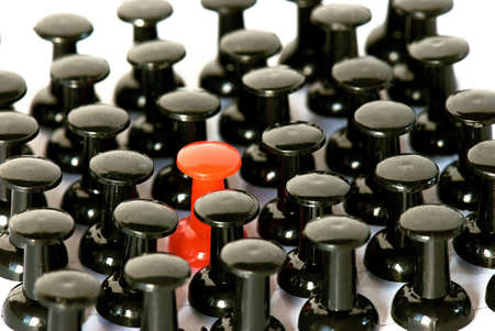 exception: Even array of black pushpin and one red pushpin close-up