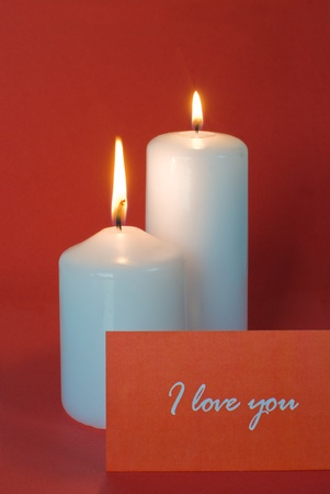 two burning candles and red card on a red background Stock Photo - 17727980