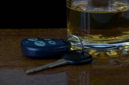 glass of alcohol and car keys on the bar photo