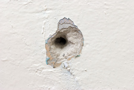 Deep circular hole in the plaster wall covered with peeling paint