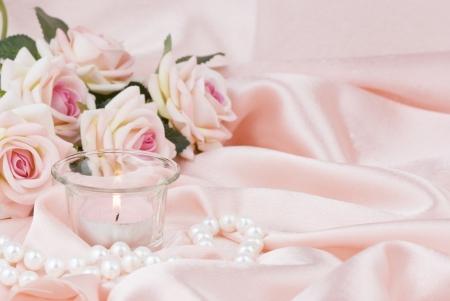 rosa Rosen, brennende Kerze und eine Perlenkette auf einem Seidenstoff Standard-Bild