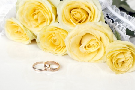 ruche: Bouquet of yellow roses and wedding rings on a white background