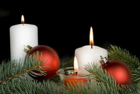 Christmas composition with a burning candles on a black background photo