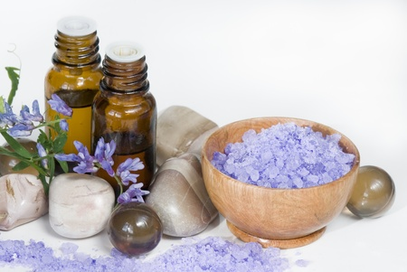 violet bath salt in wooden bowl and two vials of aromatic oil photo