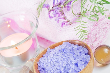 Spa setting with lilac flowers, bath salts and a candle photo