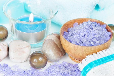 Spa setting with lilac bath salts and a burning candle