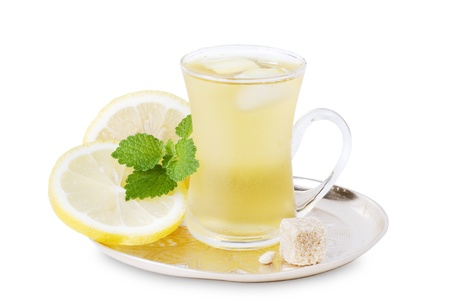 misted: Misted glass cup of cold green tea with ice, lemon, sugar and mint on a white background Stock Photo
