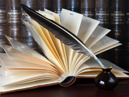 Feather in the inkwell and an open book on a dark shelf of old books