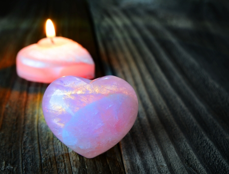 warm heart - a burning candle and a cold heart - rose quartz Stock Photo - 25126687