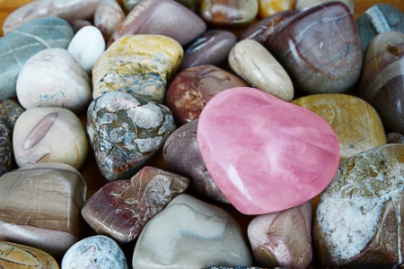 rose quartz heart on multicolored background sea pebbles Stock Photo