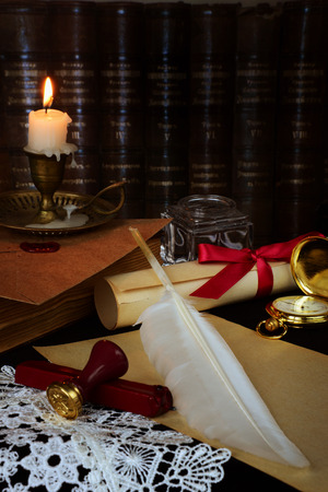 still life with a letter, a pen, a lighted candle in copper candlestick on a background of old books  photo