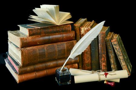 Stilleben mit einem Buchstaben, einer Feder und alte Bücher auf einem schwarzen Hintergrund
