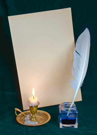 White feather in the inkwell, burning candle and old paper on dark-green cloth