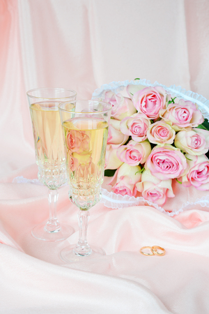 Bouquet of pink roses, wedding rings and two glasses of white wine on satin fabric  photo