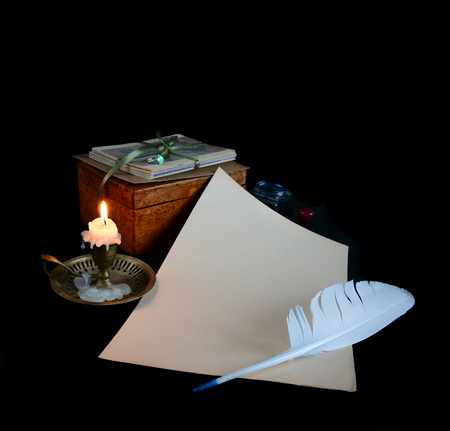 well read: Still life with a letter, a pen, a lighted candle in copper candlestick on a dark  Stock Photo