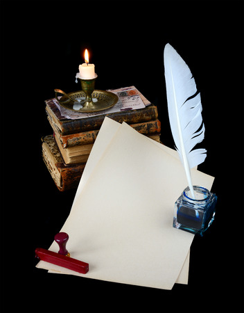 well read: Still life with a letter, a pen, a lighted candle in copper candlestick and a pile of old books on a dark