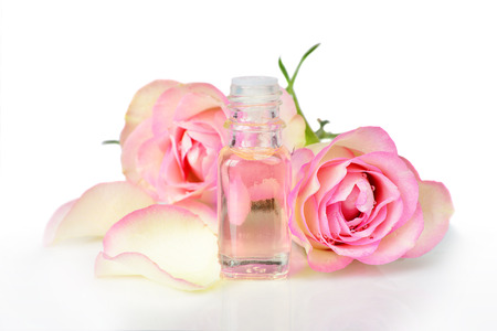 perfume oil: Vial with essential oil and two roses on a white