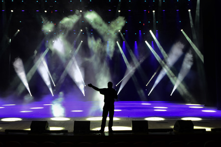concert stage: Singing man silhouette on a brightly lit concert stage
